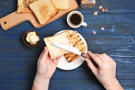 Mujer untar mantequilla sobre pan tostado sobre la mesa, vista superior