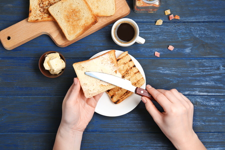 Woman spreading butter on toasted bread over table, top view Stok Fotoğraf