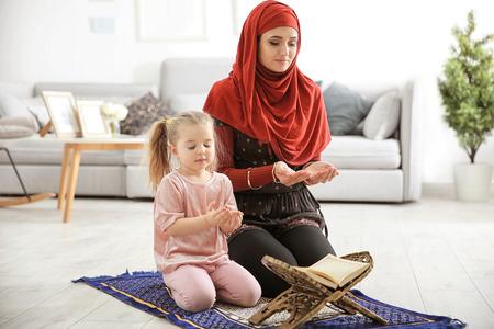 Femme musulmane priant avec sa fille à la maison Banque d'images