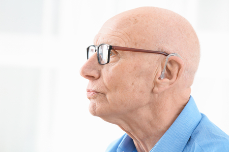 Senior man with hearing aid on light background
