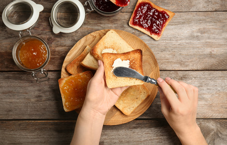 Woman spreading butter on toasted bread over table, top view Stock Photo