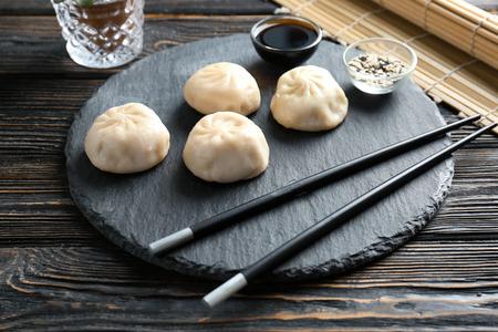 Slate plate with tasty baozi dumplings, sesame and soy sauce on table