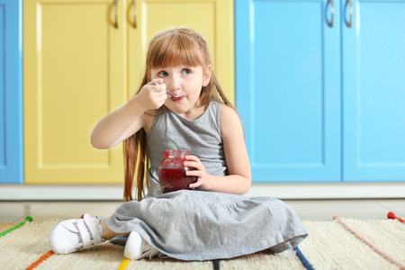 Cute little girl eating jam at home