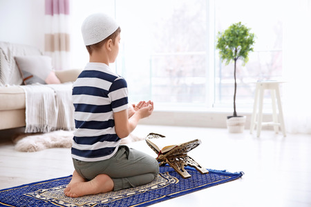 Muslim boy praying on rug at home 写真素材