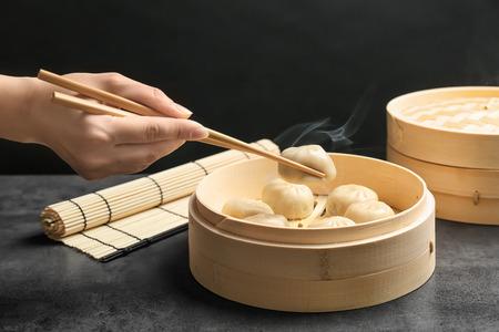 Mujer con sabrosas bolas de masa de baozi en vaporizador de bambú en la mesa