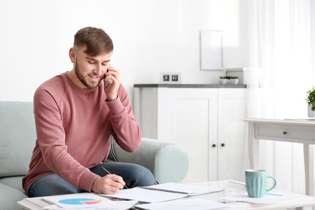 Young man talking on mobile phone while working at home