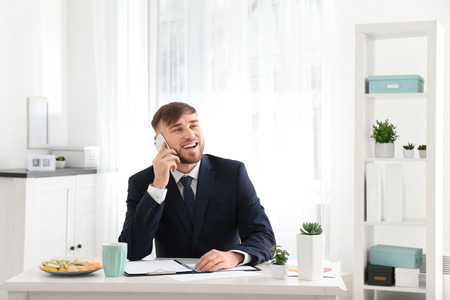 Young businessman talking on mobile phone while working in office