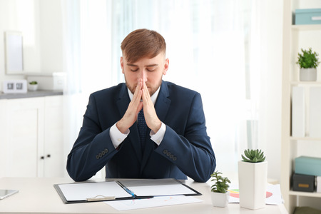 Religious young businessman praying at table in office