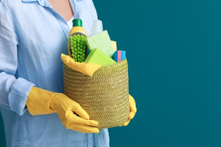 Woman holding basket with cleaning supplies on color background