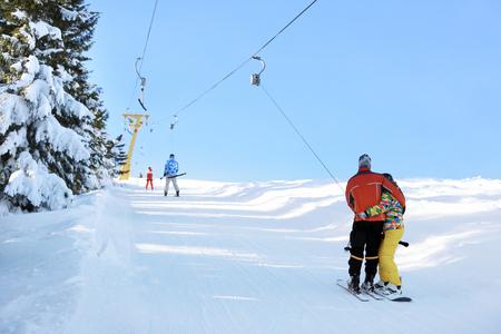 Couple using ski lift at snowy resort. Winter vacation