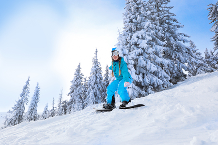 Female snowboarder on ski piste at snowy resort. Winter vacation Imagens