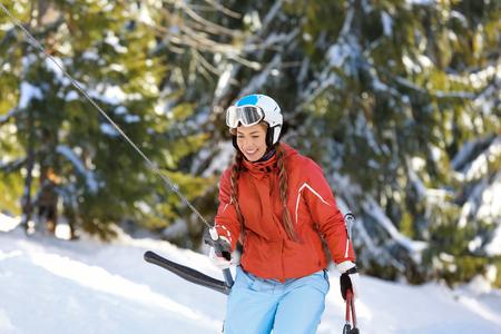 Woman using ski lift at snowy resort. Winter vacation