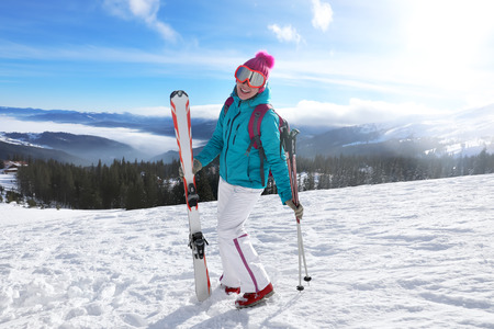 Happy woman on ski piste at snowy resort. Winter vacation