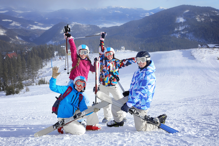 Amici felici sulla pista da sci al resort innevato. Vacanze invernali