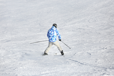 Man skiing on piste at snowy resort. Winter vacation