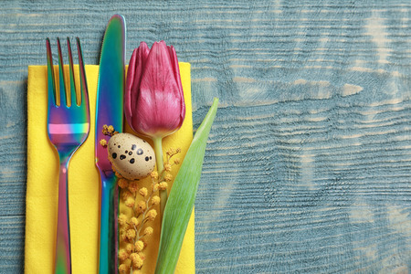 Beautifully decorated cutlery for Easter table setting on wooden background Standard-Bild