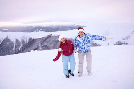 Happy couple in Santa hats having fun at snowy resort. Winter vacation