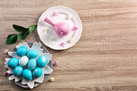 Bird figure and dyed Easter eggs on table, top view Stock Photo