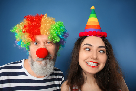 Young woman and mature man in funny disguise on color background. April fools day celebration