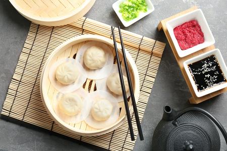 Bamboo steamer with tasty baozi dumplings on table
