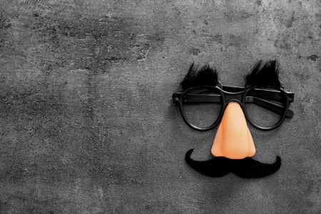 Funny glasses on grey background. April fool's day celebration