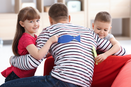 Little kids sticking paper fish to their father's back indoors. April fool's day prank Stock Photo