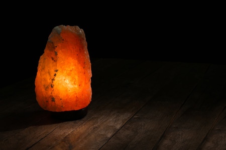 Himalayan salt lamp on table against dark background