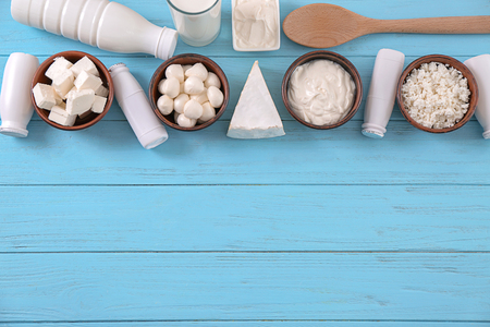 Dairy products on color wooden background
