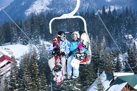 Couple on ski lift at mountain resort. Winter vacation Standard-Bild