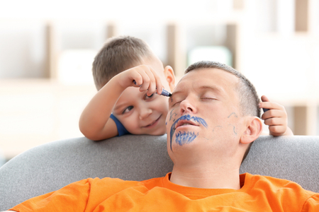 Little boy painting his fathers face while he sleeping. April fools day prank