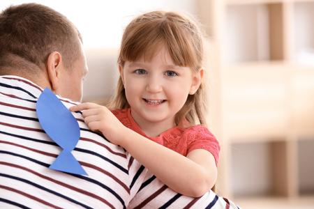 Niña pegando peces de papel a la espalda de su padre en el interior. Broma del día de los inocentes