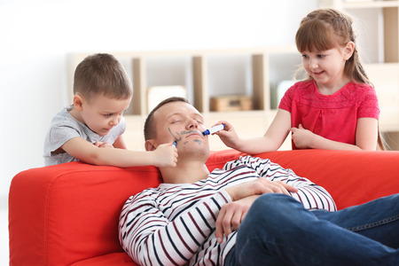 Little children painting their father's face while he sleeping. April fool's day prank Stock Photo