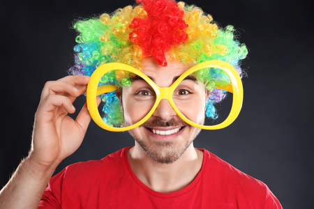 Young man in funny disguise on grey background. April fools day celebration