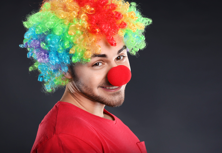 Young man in funny disguise on grey background. April fool's day celebration Banco de Imagens