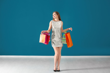 Beautiful young woman with shopping bags against color wall 写真素材