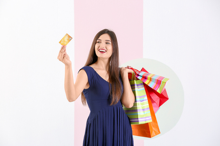 Beautiful young woman with shopping bags and credit card on color background