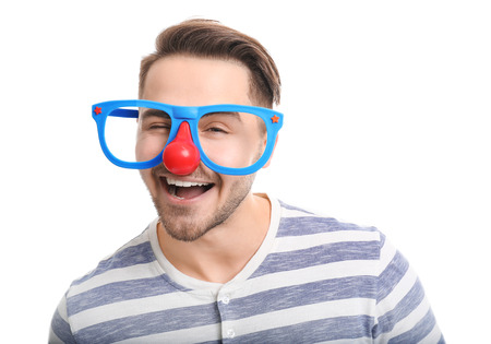 Young man in funny glasses on white background. April fools day celebration Imagens