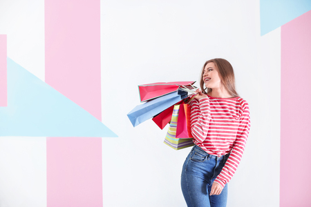 Beautiful young woman with shopping bags on color background 写真素材