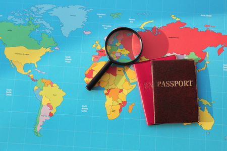 Magnifying glass, passports on world map. Immigration concept 免版税图像