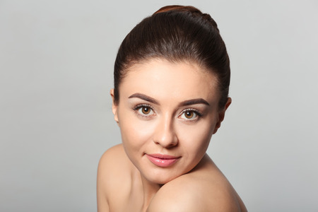 Beautiful young woman with silky skin after spa treatment on light background Imagens
