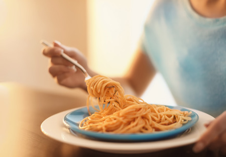 Young woman eating tasty pasta at table, closeup