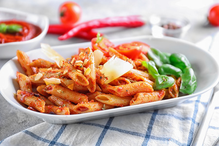 Plate with delicious penne pasta and garnish on table