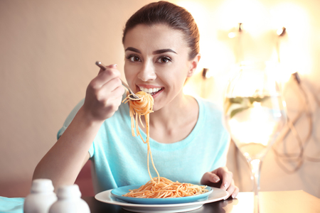 Young woman eating tasty pasta in cafe Archivio Fotografico