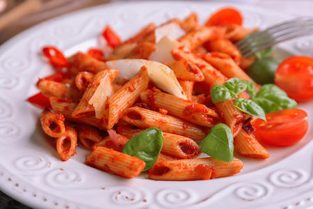 Plate with delicious penne pasta and garnish, closeup 免版税图像