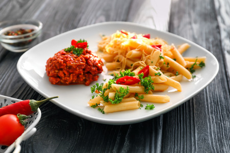 Plate with tasty penne pasta and bolognese sauce on wooden table