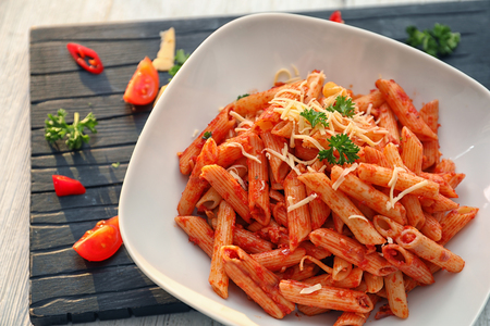 Plate of tasty penne pasta with tomato sauce on table
