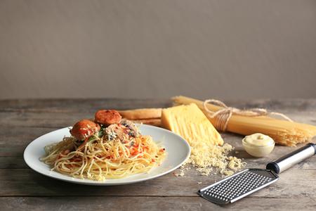 Piatto di pasta deliziosa con carne e funghi sulla tavola di legno