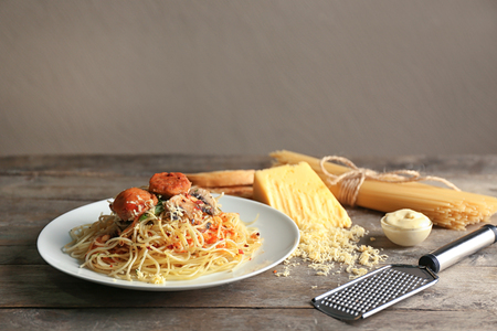Plate of delicious pasta with meat and mushrooms on wooden table