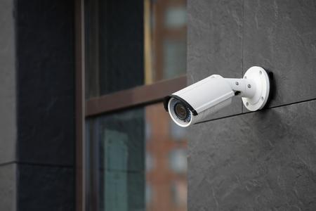 Cámara CCTV moderna en la pared del edificio al aire libre