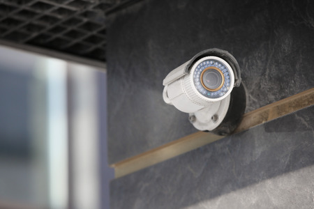 Modern CCTV camera on wall of building outdoors